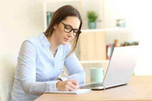 Frau am Schreibtisch, die sich Notizen macht.